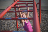Little girl Going Swinging Across Monkey Bars