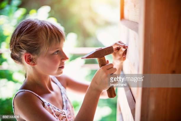 Meisje een nagel hameren