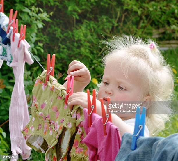 Little girl hanging clothes on washing line