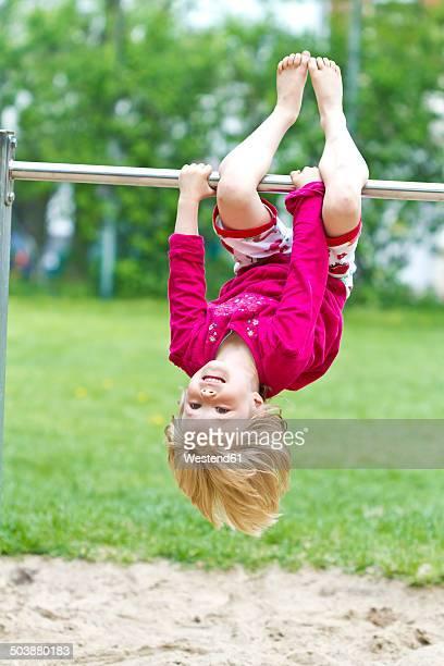 Little girl hanging head first at bar