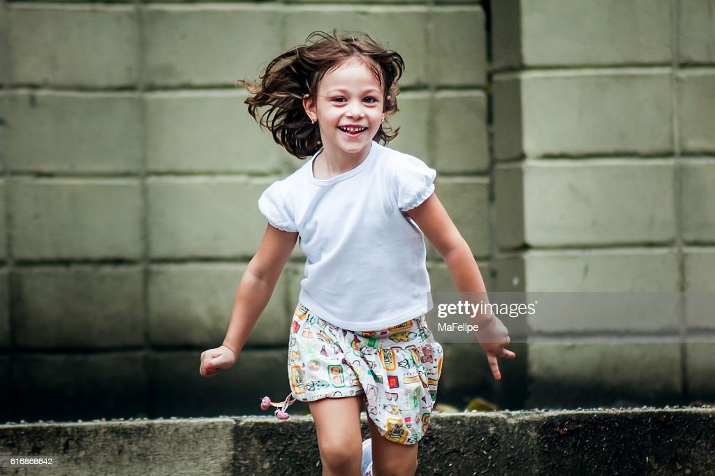 Little Girl Happily Running Towards Camera : Stock Photo