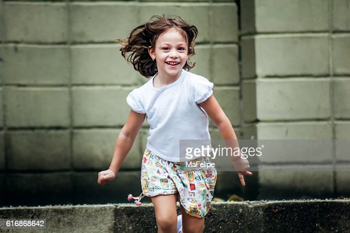 Little Girl Happily Running Towards Camera : Stock Photo