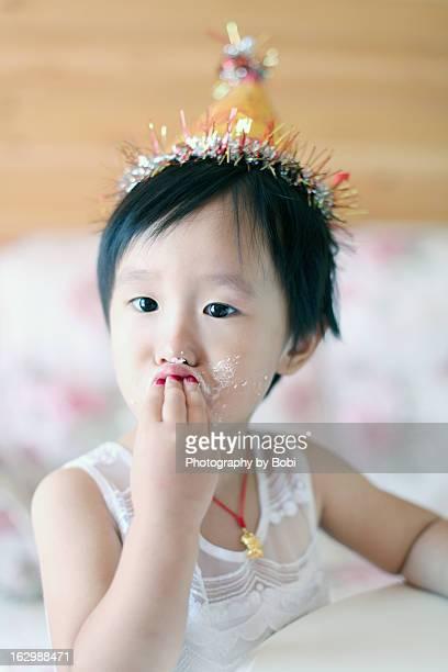 little girl happy to eat birthday cake