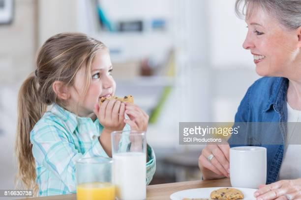 Little girl has cookies and milk after school