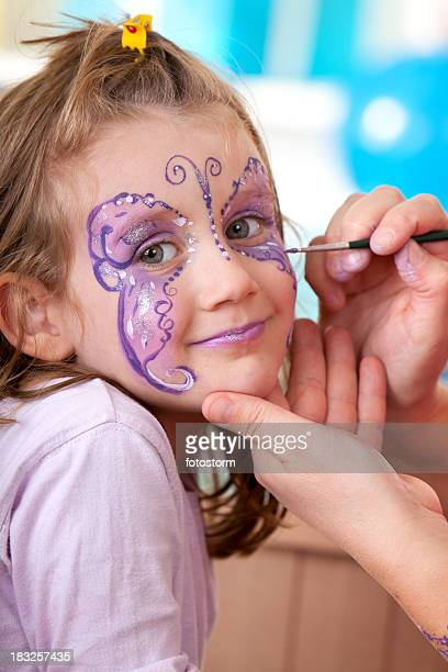 Little girl having face painted on birthday party