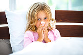 Photo of little girl sitting on white bed in morning. Girl having runny nose