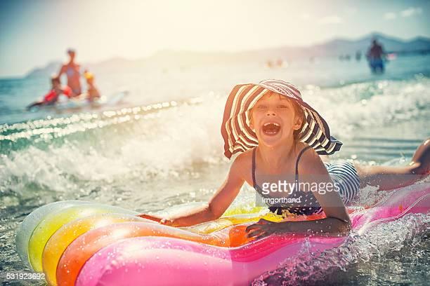 Piccola bambina divertirsi in mare sul materasso gonfiabile aria