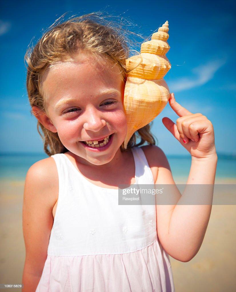 Little girl having fun on a beach : Stock Photo