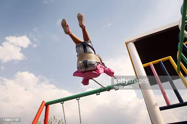 Little girl having fun on a swing.