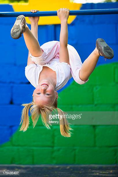 Little girl having fun on playground gymnastics bar
