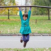 Little girl having fun on playground gymnastics bar.