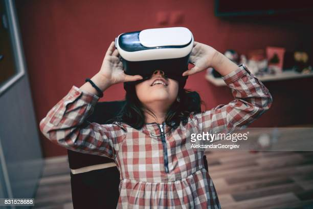 Little Girl Having Fun with Virtual Reality Simulator and Gesturing