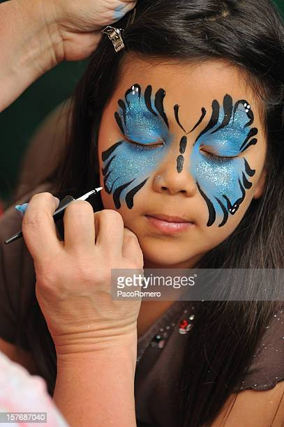 Little girl having her face painted.