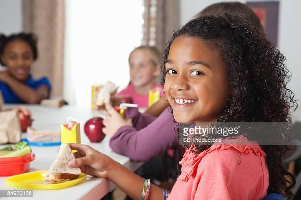 小さな女の子が学校教室での昼食