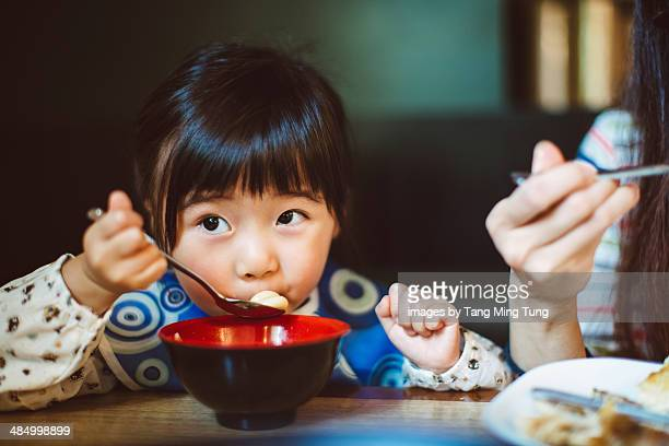 Little girl having meal with mom in restaurant