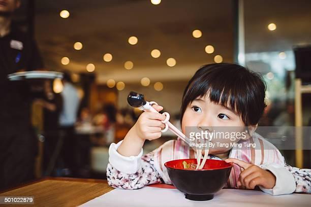 Little girl having noodles in restaurant