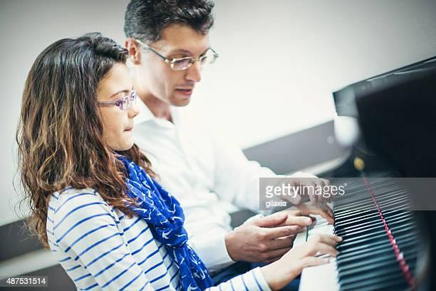 Little girl having piano class with her teacher.