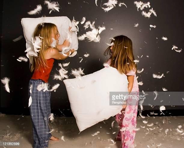 Little girl having pillow fight