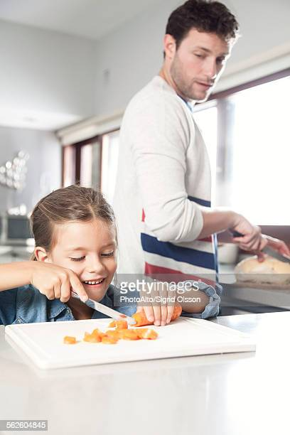 Little girl helping her father prepare food in kitchen