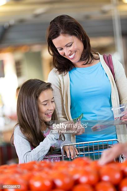 Little girl helping mother shop for groceries and use coupons