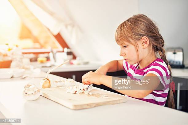 Little girl helping to prepare a meal