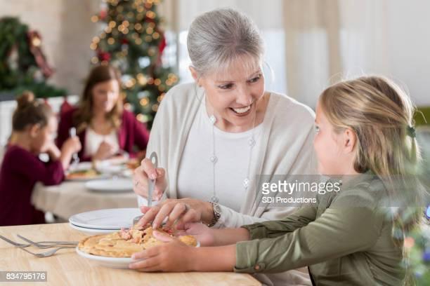 Petite fille aide grand-mère servir la tarte le jour de Noël