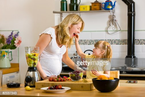 Little girl helps her mother preparing fresh fruit smoothie. : Stock Photo