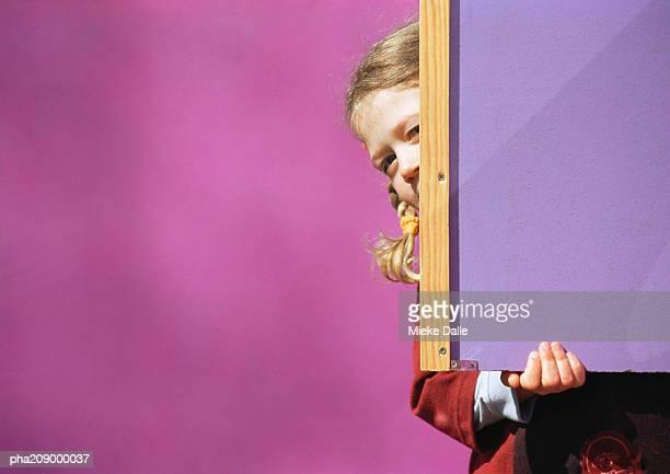 Little girl hiding behind chalkboard.