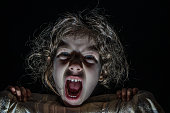 Headshot of little girl  hiding behind her bed sheets and screaming