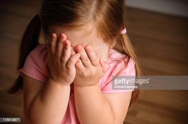 Petite fille se cacher son visage entre caméra