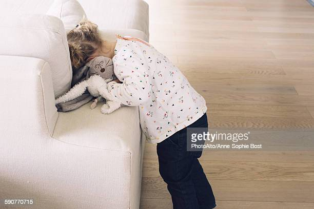 Little girl hiding her face in sofa cushions