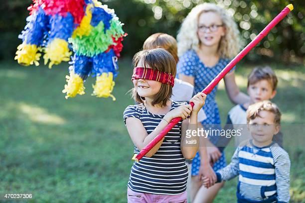 Petite fille frapper la pinata au parti