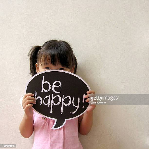 A little girl holding a 'Be Happy' sign
