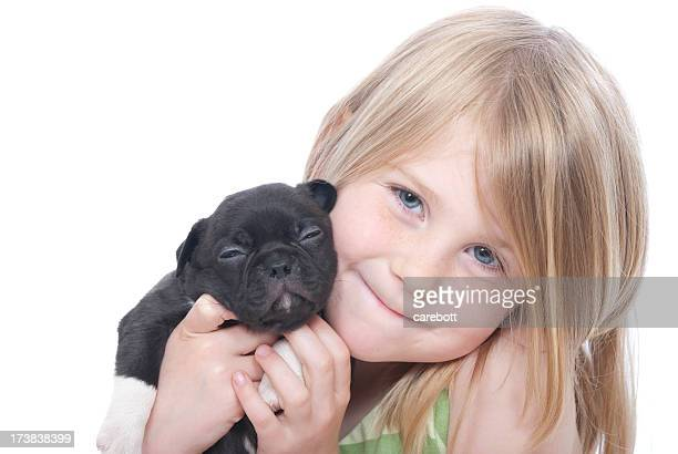 A little girl holding a black puppy on a white background
