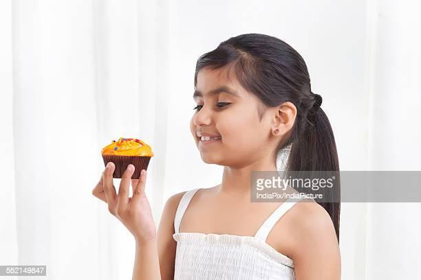 Little girl holding a cupcake
