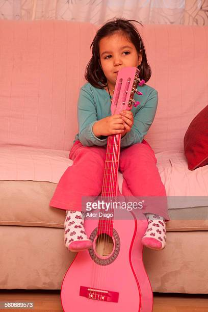 Little girl holding a guitar while thinking.