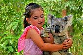 Little girl (age 05) holding a Koala in  Gold Coast Queensland, Australia.