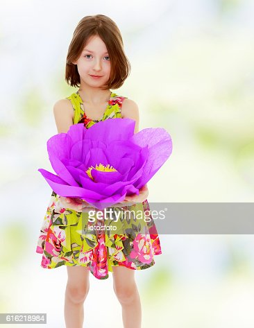 Little girl holding a large purple flower : Stock Photo