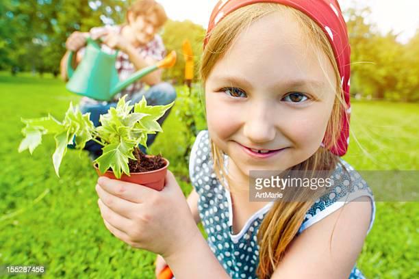 Kleines Mädchen hält eine Pflanze in einem kleinen Topf