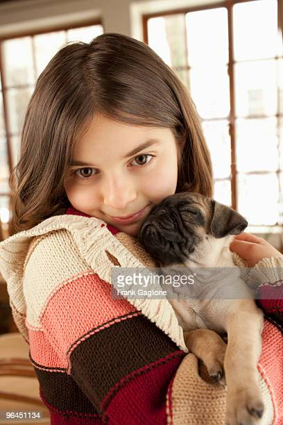 Little Girl Holding a Pug Puppy.