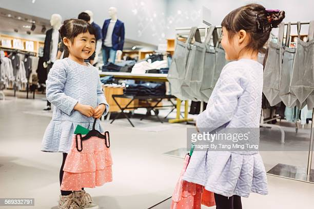 Little girl holding a skirt in front of mirror