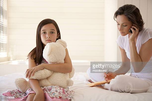 Little Girl Holding a Teddy Bear While Her Mother Talks on the Phone