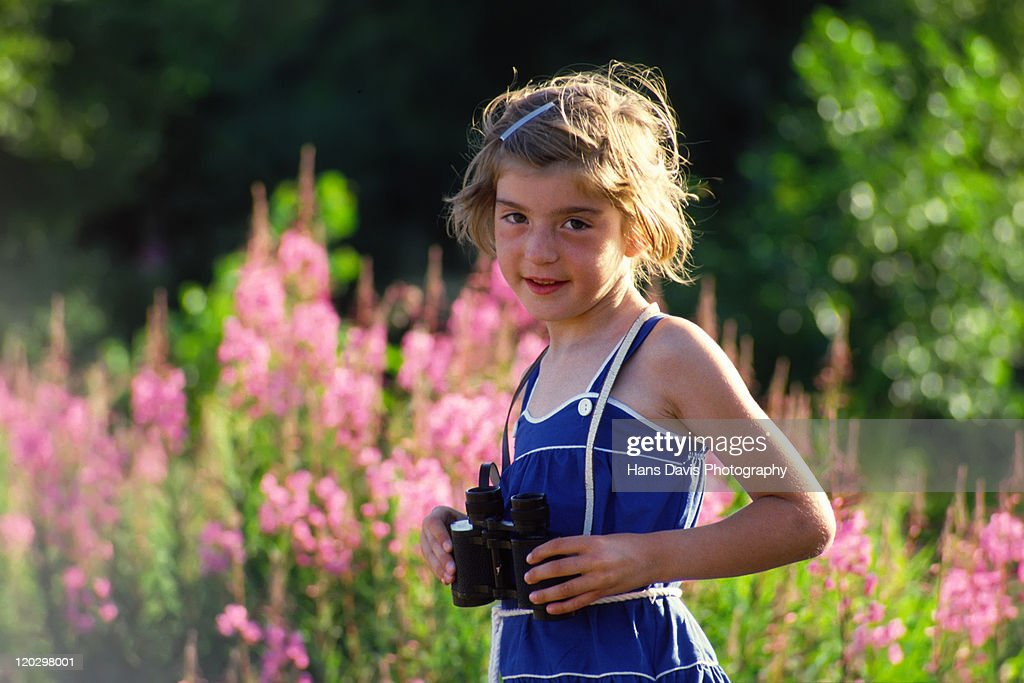 Little girl holding binoculars : Stock Photo