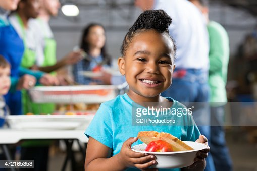 Little girl holding bowl at soup kitchen or food bank