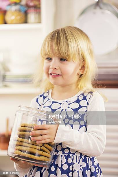 Little Girl Holding Chocolate Chip Cookie in a Jar