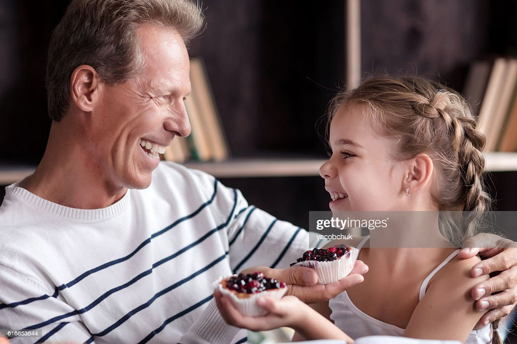 Little girl holding cupcakes with her grandfather : Stock Photo