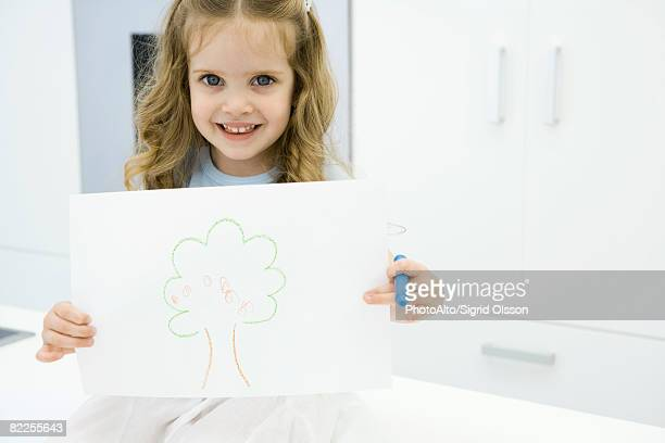 Little girl holding drawing of tree, smiling at camera