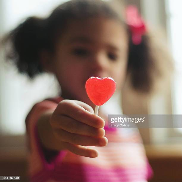 Little girl holding heart shaped lollypop