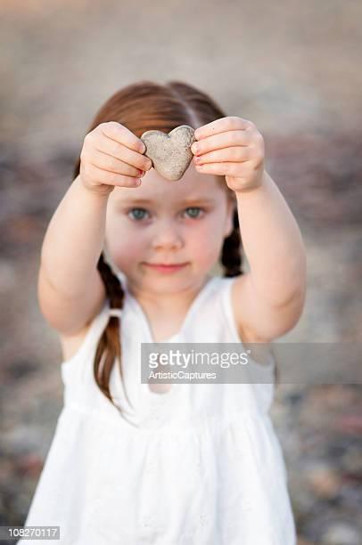 Little Girl Holding Heart-Shaped Rock