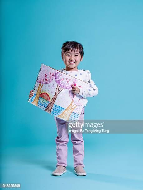Little girl holding her drawing smiling joyfully